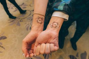 Multi-color wedding temporary tattoos on wrist of man and woman