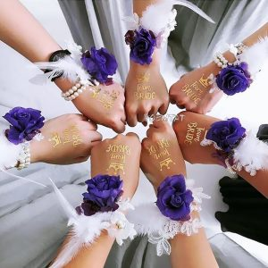 Bridesmaids sporting rosettes and team bride temporary tattoos interlock fists